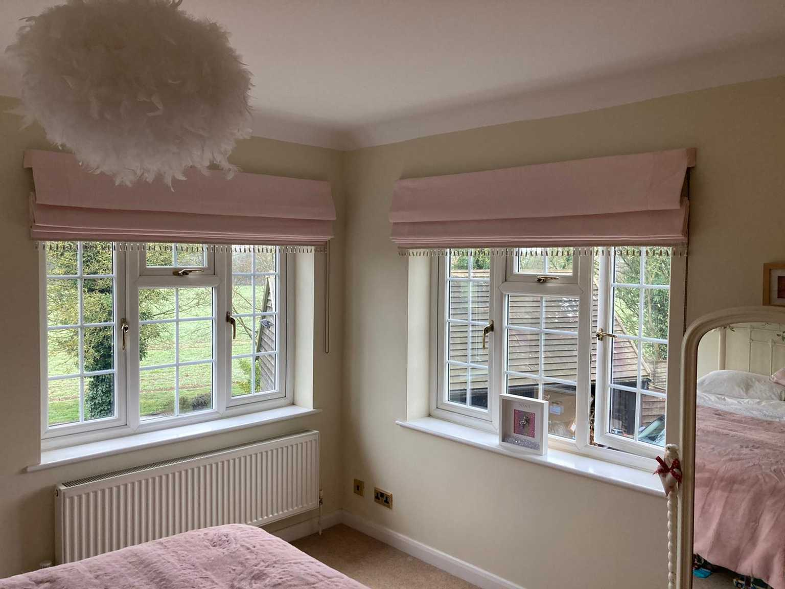 Little girls pale pink roman blinds with bobble trim